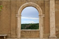 Italian view through the arch window in Sorano, Tuscany, Italy. Medieval wall with arch window in Italy Stock Image