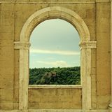 Italian view through the arch window in Sorano, Tuscany, Italy. Medieval wall with arch window in Italy Royalty Free Stock Photos