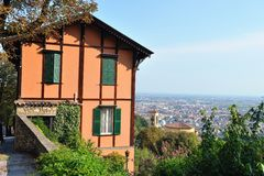 Italian villa overlooking Bergamo, Lombardy, Italy. Pretty apricot orange coloured northern Italian villa on a hill overlooking Bergamo, Lombardy, Italy and the Royalty Free Stock Image