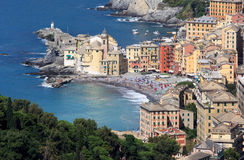 Italian village Camogli along the Golfo Paradiso. Sunbathers in the Italian village of Camogli, situated on on a rocky outcrop on the west side of the peninsula Royalty Free Stock Photos