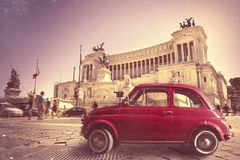 Italian vintage retro old red car. Monument in Piazza Venezia, Rome Italy Stock Photography