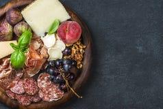 Italian wine snacks variety over dark plywood background, copy space royalty free stock photo