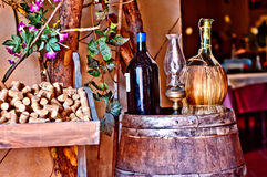 Italian winery with bottle and bottle of wine. Wine bottles, with bottle of olive oil, resting on an oak barrel cellar in a typical Italian Royalty Free Stock Photos