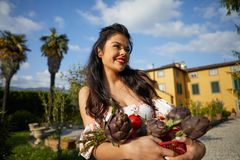 An Italian woman, a housewife, collects vegetables for dinner in a home garden.  stock images