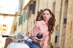 Italian woman sitting on a vintage  scooter. Royalty Free Stock Images