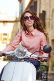 Italian woman sitting on a vintage  scooter. Royalty Free Stock Photography