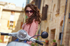 Italian woman sitting on a vintage  scooter. Royalty Free Stock Photo