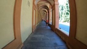 Italian woman walking. Under San Luca`s longest archway in the world leading to the San Luca Sanctuary of Bologna city in Italy stock image