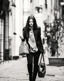 Italian Woman. A young beautiful dark hair woman with a handbag walking with intent in the beautiful narrow streets of Genoa, an old Italian harbor city royalty free stock photo