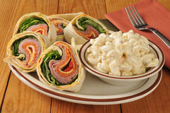 Italian wrap sandwich with macaroni salad. Sliced Italian wrap sandwich on a rustic table with macaroni salad Royalty Free Stock Image