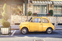 Italian yellow car parked in street. Picture of yellow Fiat 500 parked in Italian street Royalty Free Stock Images
