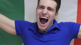 Italian Young Man Celebrates holding the Flag of Italy in Slow Motion. High quality stock photos