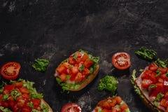 Italiano Bruschetta con los tomates, la salsa de la mozzarella y las hojas tajados de la ensalada Aperitivo o bocado italiano tra imagen de archivo