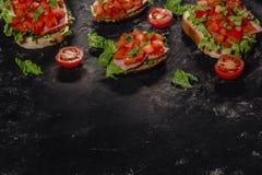 Italiano Bruschetta con los tomates, la salsa de la mozzarella y las hojas tajados de la ensalada Aperitivo o bocado italiano tra foto de archivo libre de regalías
