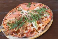 Italiano cocido delicioso Salmon Pizza en la tabla de madera fotografía de archivo