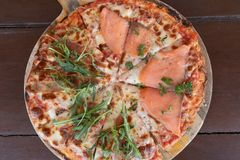 Italiano cocido delicioso Salmon Pizza en la tabla de madera foto de archivo
