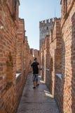Italiano de Castelvecchio: Opinião velha do tijolo do ` do castelo do ` as paredes e um turista que acordam com sua câmera fotos de stock royalty free