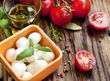 Italiano que cozinha ingredientes, mussarela, manjericão, e Cherry Tomat Fotografia de Stock Royalty Free