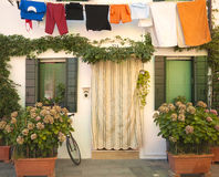 Italien Burano: hus med blommor och att hänga för tvätteri Royaltyfri Foto
