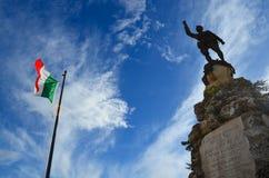Italien flagga bredvid WWI-monumentet i Cisternino, Puglia royaltyfria foton