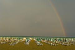 Italien Lignano strand med sunloungers, regnbåge i bakgrund Fotografering för Bildbyråer