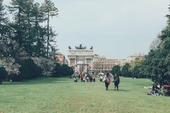 Italien Milan, April 6, 2018: Folket går i parkerar på gräsmattan royaltyfri bild