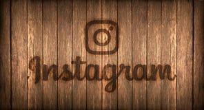 Italien november 2016 - den Instagram logoen skrivev ut på brand på ett trä Arkivbild