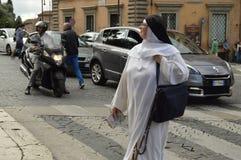 Italien Rome Oktober 07,2018 En nunna i vit kläder som promenerar en övergångsställe i mitten av Rome som rymmer royaltyfri foto