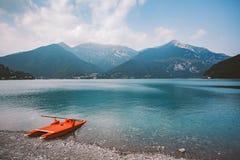 Italien sikt av ett berg sjö lago di ledro med en strand och en livräddningsbåtkatamaran av röd färg i sommar i molnigt väder royaltyfri fotografi