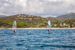 ITALIEN två man vindsurfa Sardinia på blått vatten framme av den steniga kusten Arkivfoto