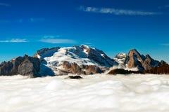 Italienare Dolomiti - det Marmolada maximumet dyker upp från molnen royaltyfri fotografi
