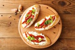 Italienare skjuter in - bruschetta med ost, tomaten och basilika Arkivfoton