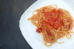 Italienare Spagetthi Bolognese med tomater kryddad sås i den isolerade vita plattan arkivfoto