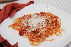 Italienare Spagetthi Bolognese med tomater kryddad sås i den isolerade vita plattan arkivbild