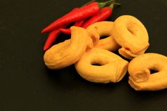Italienare Tarallini med röda peppar kritiserar på bakgrund Royaltyfri Fotografi