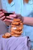 ItalienareBiscotti kakor i en exponeringsglaskrus och en kvinna med en kopp te royaltyfri fotografi