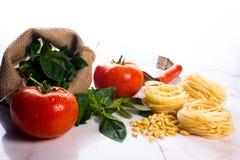 Italiener, der Bestandteile auf einer weißen Marmortischplatte kocht. Lizenzfreies Stockfoto