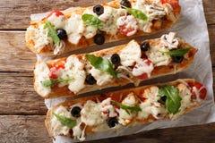 Italiener schiebt Pizzakasserolle ein: schneiden Sie das Stangenbrot, das mit Chic gebacken wird lizenzfreie stockfotografie