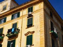 Italienische Architektur, gelbes Gebäude, grüne Fensterläden Stockbilder