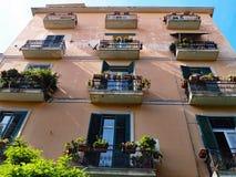 Italienische Architektur, rosa Gebäude, schwarze Fensterläden Stockbild