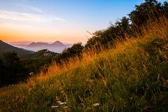 Italienische Berglandschaft mit Feld des Grases bei Sonnenuntergang stockfotos