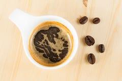 Italienische Draufsicht der EspressoKaffeetasse nahe Bohnen, Zeit der Kaffeepause Stockfotos