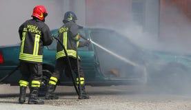 Italienische Feuerwehrmänner löschten das Autofeuer nach dem Autounfall aus Stockbilder