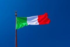 Italienische Flagge, die im Wind auf dem Fahnenmast mit blauem Himmel flattert Lizenzfreie Stockfotografie