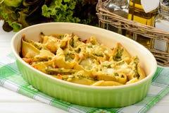Italienische Küche - Teigwarenoberteile angefüllt mit Spinat, Ricotta und mit Tomaten gebacken Stockbild