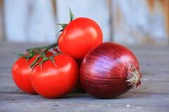 Italienische Kirschtomaten und rote Zwiebel auf einem Holztisch Lizenzfreie Stockfotografie