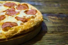 Italienische Pepperonipizza mit Salami auf dunklem hölzernem Hintergrund Italienische traditionelle Nahrung Ein strukturierter Hi Stockbilder