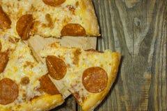 Italienische Pepperonipizza mit Salami auf dunklem hölzernem Hintergrund Italienische traditionelle Nahrung Ein strukturierter Hi Lizenzfreie Stockfotografie