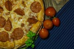 Italienische Pepperonipizza mit Salami auf dunklem hölzernem Hintergrund Italienische traditionelle Nahrung Ein strukturierter Hi Lizenzfreies Stockbild