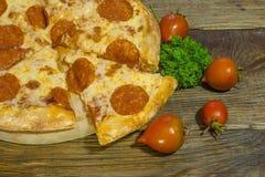 Italienische Pepperonipizza mit Salami auf dunklem hölzernem Hintergrund Italienische traditionelle Nahrung Ein strukturierter Hi stockfoto